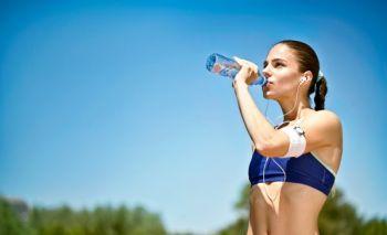 Девушка пьет воду после бега